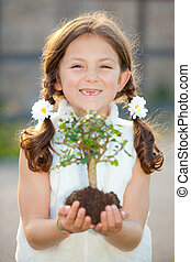 girl holding tree as invironmental or nature concept ( focus...