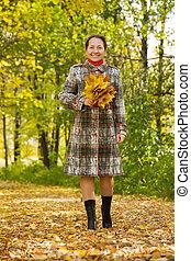 elderly woman walking in autumn park