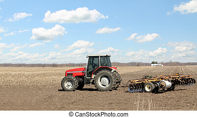 Tractor and Plow - Red farm tractor with a plow in a farm...