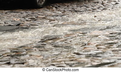 Stream of rain on the cobble road and car