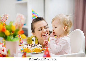 Mother spending fun time with baby on birthday party