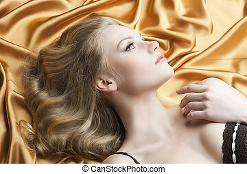 portrait of blond woman laying, she looks up at left