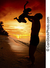 silhouette family of child hold on father hand with sea view...