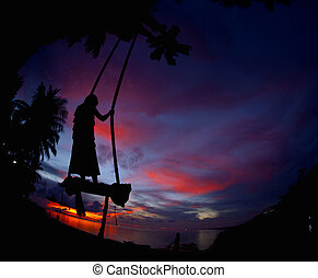 Girl swinging with the sea in the sunset background