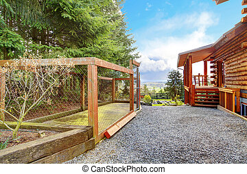 Log cabin with dogs fenced canal area behind the house. -...