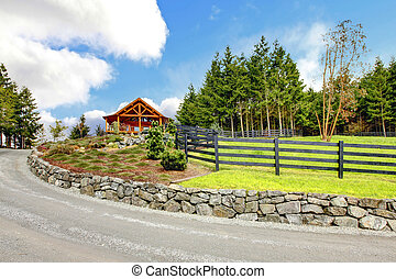 Log cabin house on the hill with road and fence