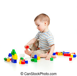 cheerful child boy playing with construction set over white...