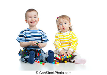 Happy children boy and girl playing together with  mosaic toy