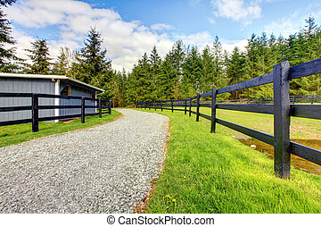 Horse farm with road, fence and shed.