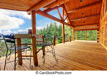 Porch of the log cabin with small table and forest view. -...