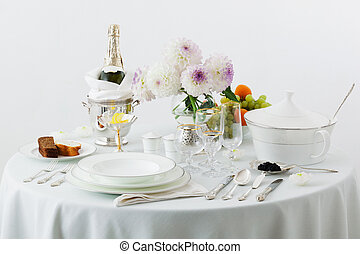 table with dishes and flowers on a white background