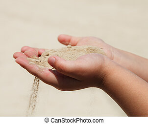 Hands of the child holding sand