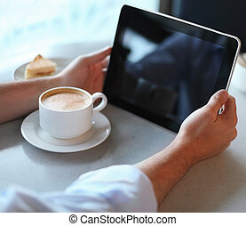 Man holding tablet computer in cafe. Close up