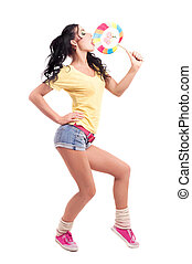 woman with candy - pretty young brunette woman eating a...