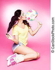 woman with lollipop - pretty young brunette woman eating a...
