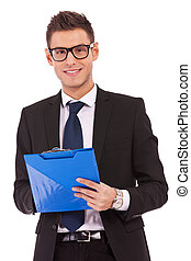 business man wearing glasses is writing on clipboard - young...