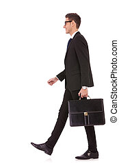 business man holding brief case and walking over white...