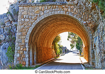 Stone tunnel at mountain road