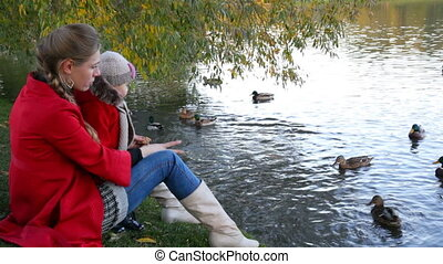 Mother with the daughter feed ducks in a pond