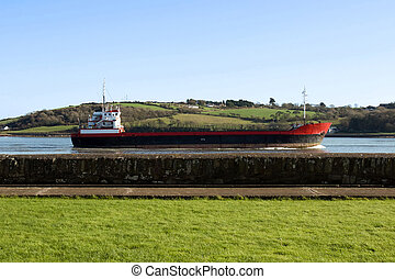 cargo ship sailing past sea wall - cargo ship sailing past...