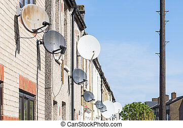 Row of satellite dishes installed in front of brick houses.