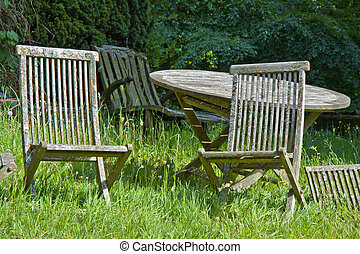 Deserted garden with old wooden table and chairs on grass