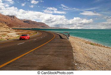 Red car on a highway. - Red car on a highway that runs along...