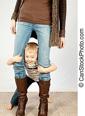 Cute blond boy and his mothers legs