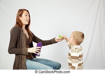 Mother blowing bubbles with son