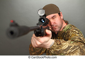 the man in a camouflage aims from a rifle with a riflescope...