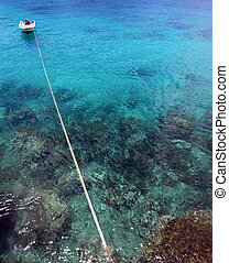 Boat on azure coral sea coast - Small boat tied on long rope...