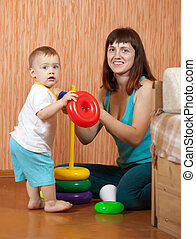 Happy mother and baby plays with toys