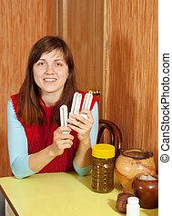 Woman holds energy   bulbs