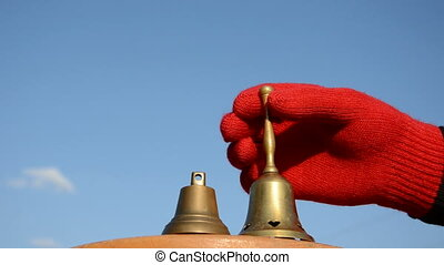 hand with brass bell and blue sky