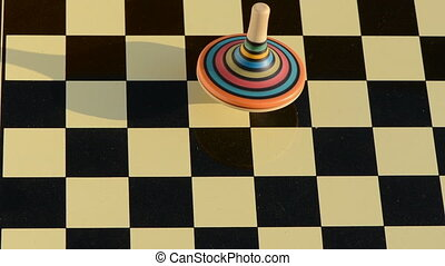 colorful wooden whirligig rotate on chessboard
