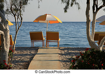 Two chairs and umbrella on the  beach . Tigaki,Greece