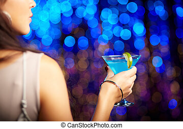 Nightlife - Rearview shot of a female with a cocktail