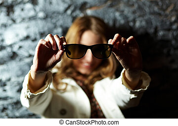 Showing sunglasses - Image of sunglasses in female hands