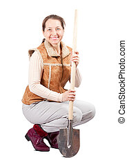 woman sits with spade over white