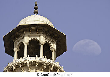 Upper part of Minaret of Taj Mahal with moon in background,...
