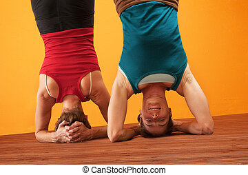 Fit Women Doing Headstands - Two women doing headstands over...