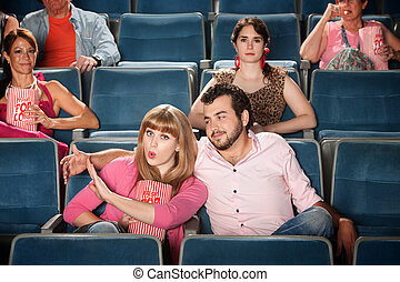 Irked Woman - Young woman annoyed with boyfriend in theater