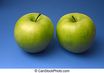 two appetizing apples of green color on a blue background