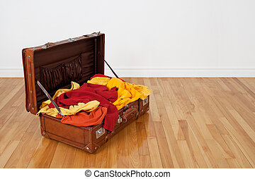 Leather suitcase full of orange and yellow clothing