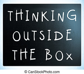 Thinking outside the box phrase, handwritten with white chalk on a blackboard