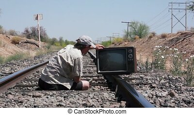 Man on Railway Tracks with Retro TV - Man sitting on the...