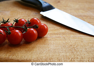 Cherry Tomatoes on a Chopping Board with Knife