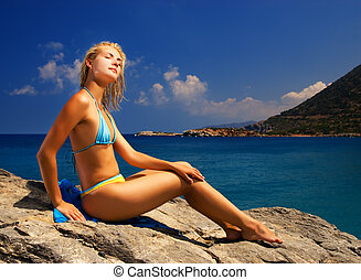 Beautiful girl relaxing near the sea