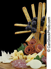 Meat delicatessen plate with cheese and grissini