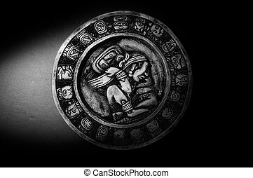 Carved Mayan calendar in dramatic light